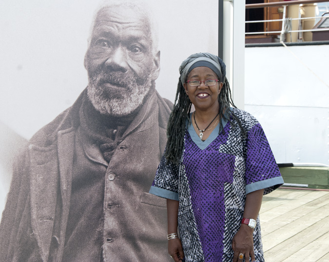 Poet, documentarian and educator Sylvia D. Hamilton stands in front of a photo of Gabriel Hall, one of 2000 former American slaves who settled in Nova Scotia and New Brunswick after the War of 1812. Photo by Joseph Muise