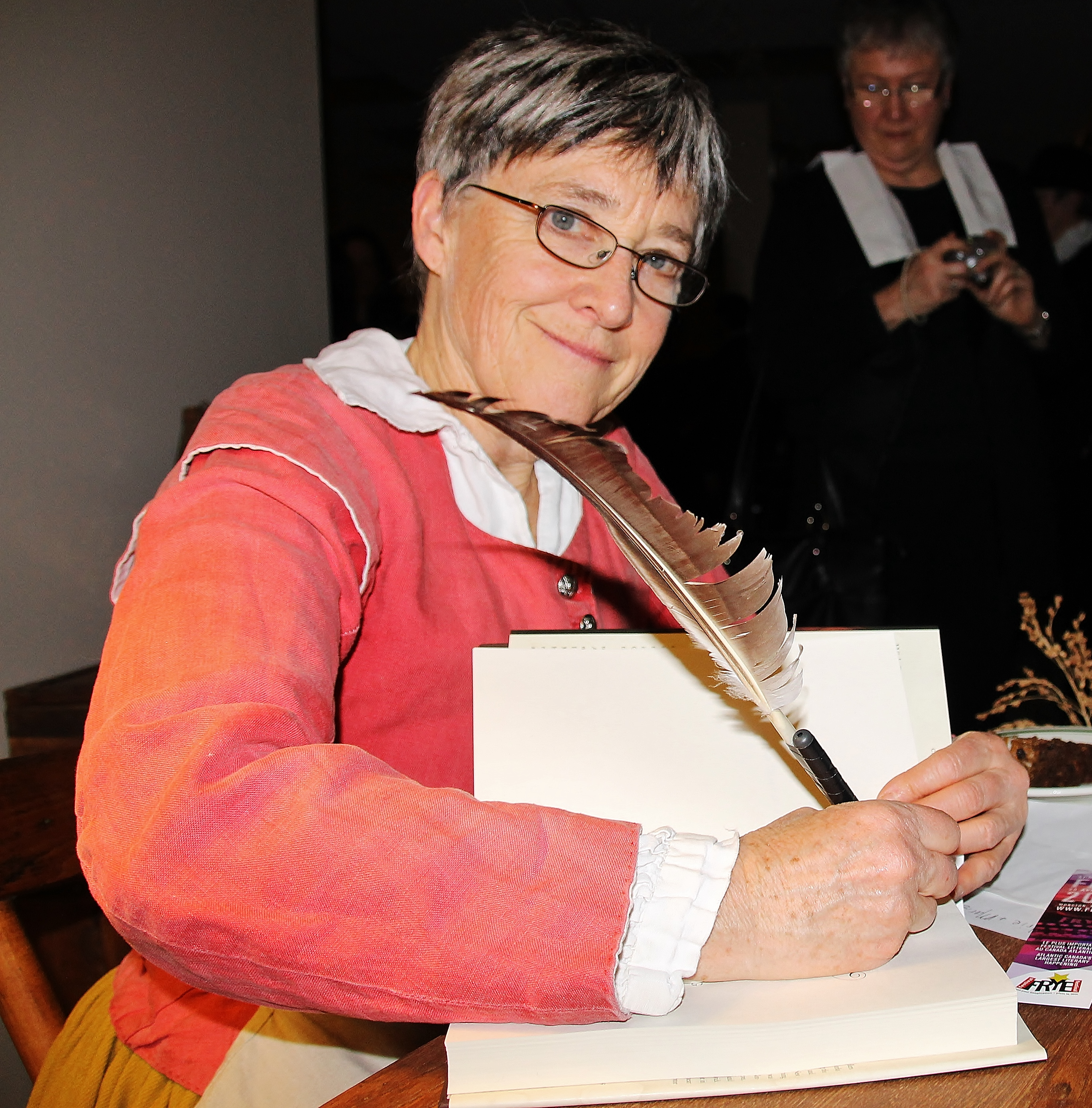 Wearing a costume lent to her by the Plymouth Plantation (Massachusetts), Beth Powning signs copies of A Measure of Light, which focuses on the remarkable life of Mary Dyer, a Puritan who fled persecution in 17th century England, only to be persecuted again in New England after joining the Quaker movement.