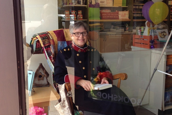 Katherine Dewar, author of Those Splendid Girls, reads in the window of Bookmark Bookstore. Photo credit: Melanie Fishbane