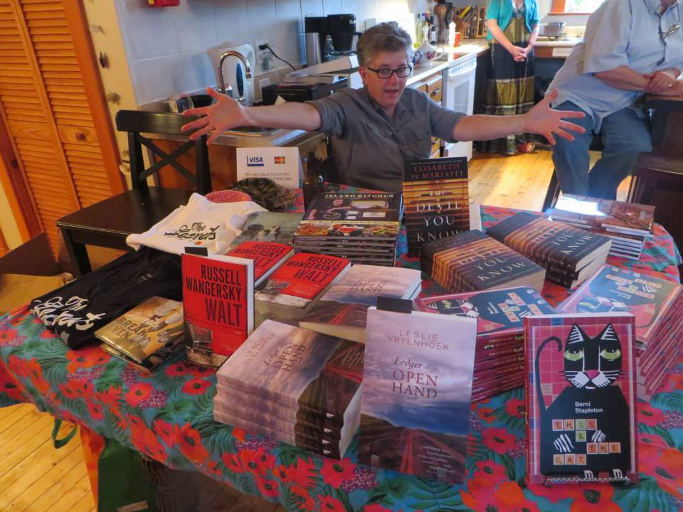 Peg Norman of the Travel Bug, The Festival at Ochre Cove's official bookseller poses with some fine Newfoundland lit. Photo courtesy of Breakwater Books.