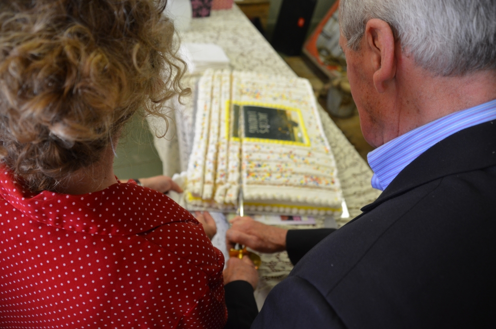 """Author Daphne Greer and her father cut the """"Jacob's Landing"""" cake (with a sword!) at the book launch in Newport Landing, NS, on Saturday, May 30. Photo courtesy of Nimbus Publishing."""