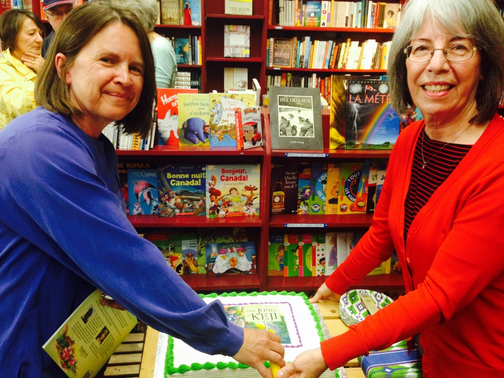 """Author Jan Coates (L) and illustrator Patsy MacKinnon (R) cut the cake at their """"King of Keji"""" book launch at the Box of Delights Book Shop in Wolfville, NS, on Saturday, June 6. Photo courtesy of Nimbus Publishing."""