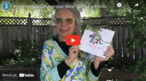 Still from a video of Marie Cadieux holding up her book, Jardin de moths